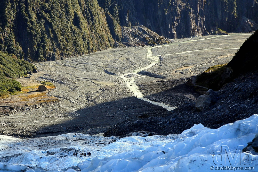 A party of climbers look very small as they descend Fox Glacier.