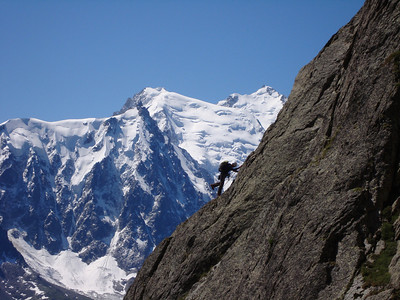 A climber on the Aiguille Rouge with the Aiguille du Midi and the Mont Blanc Massif in the background. Aiguille Rouge is where we do some of our acclimating climbs