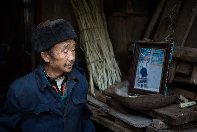 Man with a photo of his wife. Longga village, Suojia.