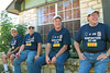 "TR07-12: Paul Senick, 1st platoon, Joe Gamache, HQ, Larry Boetsch, 1st platoon, and Jerome ""Buddy"" Meyer, 4th platoon, enjoy a laugh in the front yard. Note the T-shirts and caps Harry Thompson had made for the mini."