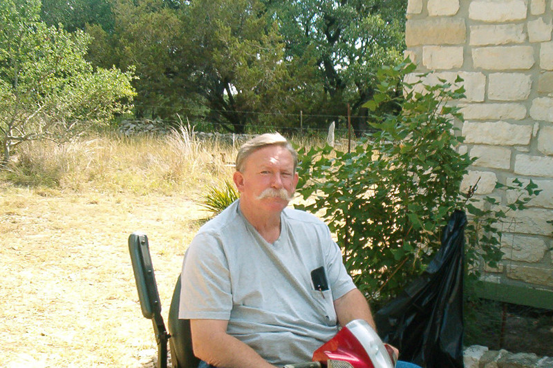 08MR-06: Alan Allen, 1st Plt, Allentown, TX, sits on his VA-supplied electric scooter in his front yard. Behind him is a Coral Bean plant, which he and Harry Thompson comfiscated at a national wildlife refuge on the Texas coast last year.