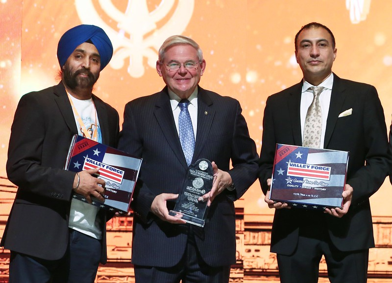 """New jersey State Sanator Bob Manendiz (Chair Senate Foreign Relations Committee ) honoring with American Flags the to host of """"Oneness"""" A light of humanity , during 550 birth Anniversary of GuruNanak celebrations in NJ on 23rd Nov 2019 in photo Onkar Singh, Senator Bob Menendez, Sukheinder Kaila ...pic Mohammed Jaffer-SnapsIndia"""