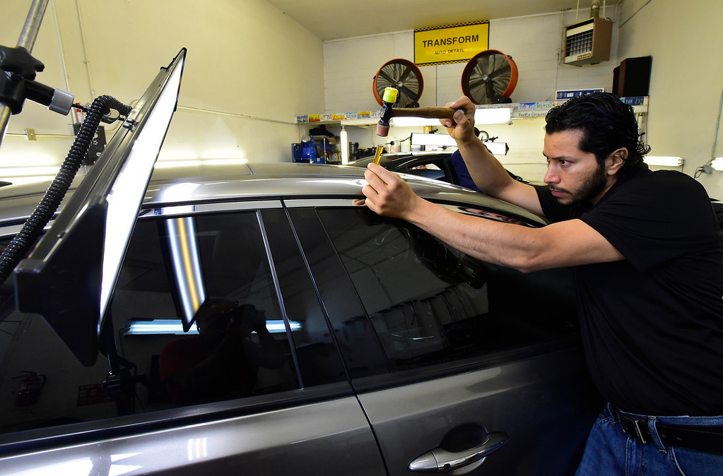 . BOULDER, CO - AUGUST 9 2018: Manny Aguirre, owner of Boulder Dents works to remove dents caused by hail at the shop in Boulder on Thursday August 9 (Photo by Paul Aiken/Staff Photographer)