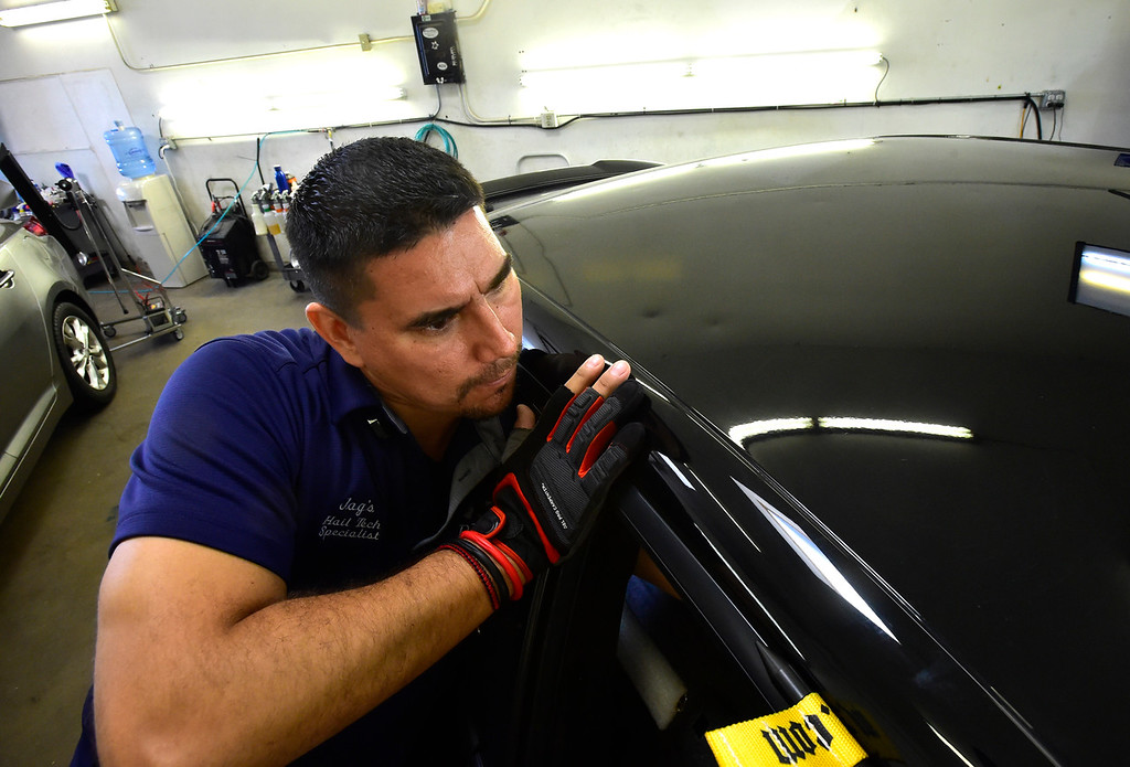 . BOULDER, CO - AUGUST 9 2018: Jose Gonzalez works to remove dents out a car\'s roof caused by hail at Boulder Dents in Boulder on Thursday August 9 (Photo by Paul Aiken/Staff Photographer)