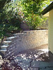 Custom retaining wall installation, including reclaimed patio pavers.