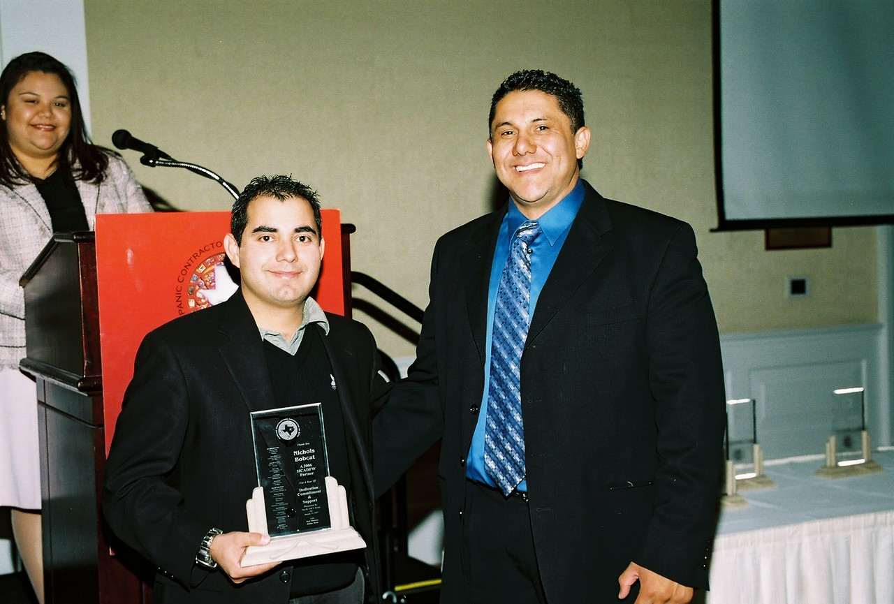 Homero Gonzalez, Nichols Bobcat accepts a HCADFW partner recognition from Javier Huerta, HCADFW Vice-Chairman