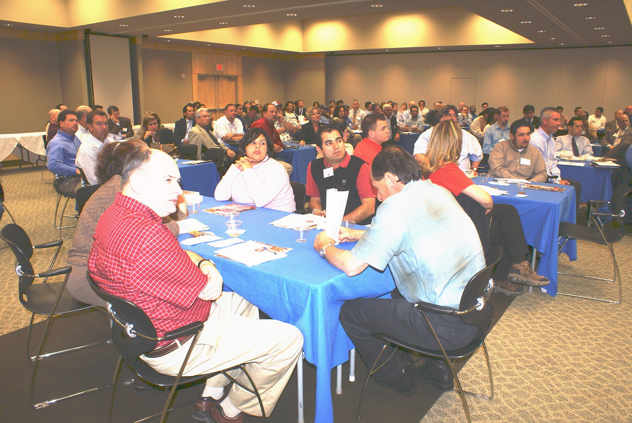 Homero Gonzales, Bobcat of Dallas (center in red shirt and black vest) at the HCADFW March 6 Procurement Luncheon.