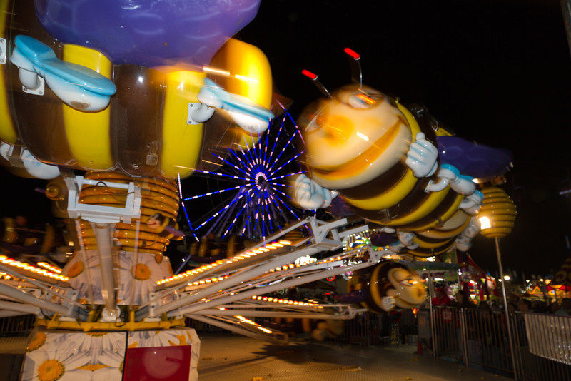 """The Bumblebee Bounce<br /> It was a long day at the rodeo and I was about to leave. I never actually saw the rodeo, but opted for the vendor area, livestock show and carnival. I figured there was enough to shoot there and I was right. I was leaving and turned for one last look and saw the ferris wheel through this """"bee"""" ride and thought I might try some motion effects. This one had just enough blur to see what it was, while still looking like it's moving."""