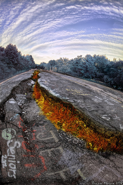 "The ""old"" Route 61 near Centralia, Pennsylvania.  The image was heavily distorted using a variety of filters and coloring techniques to achieve a ""post-apocalyptic"" feel  The cracks and warping of the road are caused by an underground mine fire, which led to nearly all of the residents of Centralia to be relocated to another area.  Route 61 now has a winding road which bypasses the area.  If you would like to read more about this photo, please visit my blog post:   http://brianmoranhdr.blogspot.com/2012/09/hot-time-in-old-town-tonight.html"