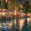 This is a shot of what you can expect to see in the evening on the Riverwalk. Lights, Texas-themed table covers, and of course a river-taxi (or tour, since they are owned by the same company)