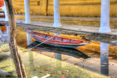 A small boat sits in a few inches of water at a Buddhist temple that was recently flooded outside Bangkok, Thailand.