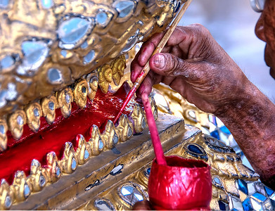 Artist paints a part of a statue at the Grand Palace in Bangkok, Thialand