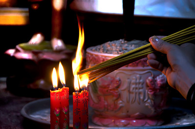 Religous ritual of lighting candles in a Buddhist temple.