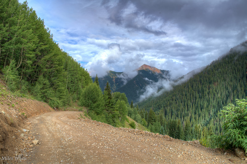 The road up to Ophir pass, with mountains in the mist.