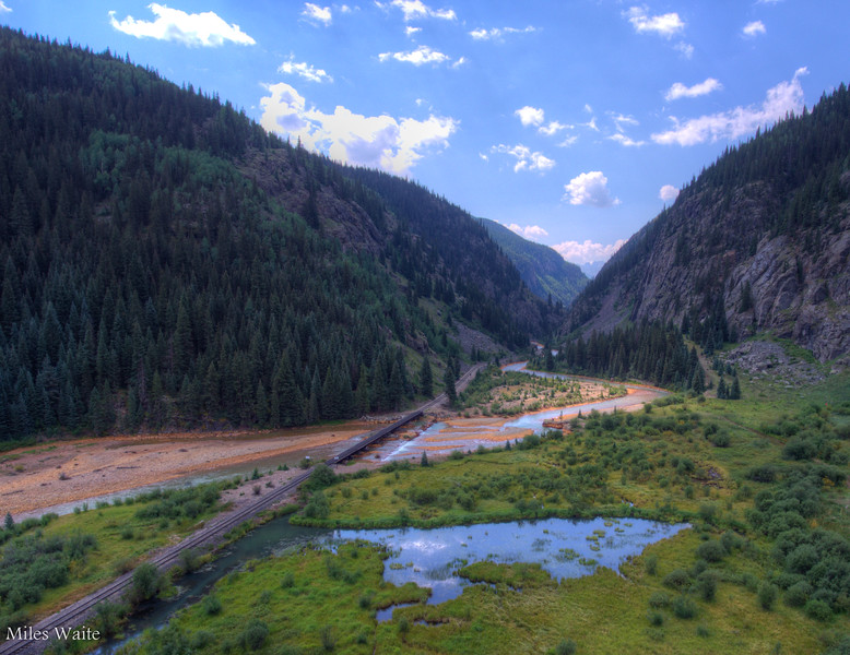 Drone shot of the Durango Silverton train tracks, coming out of the canyon and crossing over the Animas River