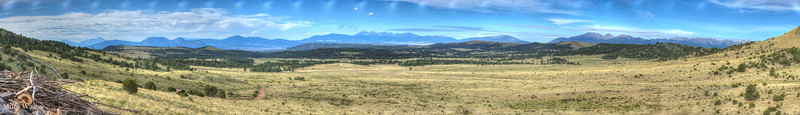 Panorama shot of the Sangre De Cristo Mountains taken from the Mission Wolf, wolf sanctuary.  The white check marks at the top seem to be from the lens adapter, Sony body. Cannon lens.