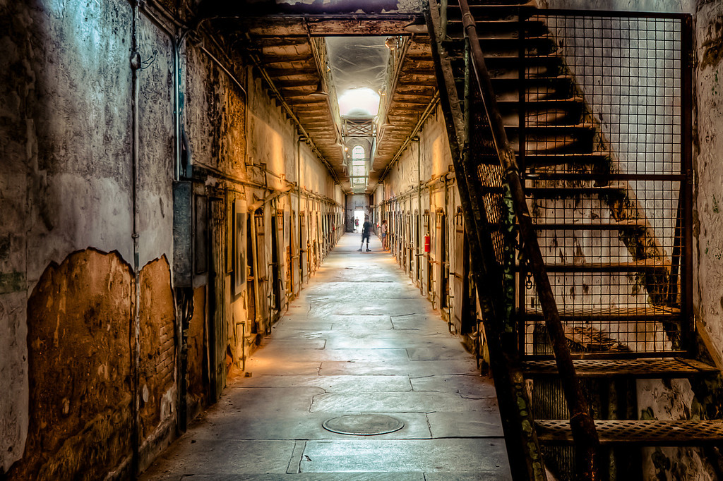 Eastern State Penitentiary (ESP)<br /> A view down one of the many creepy corridors.<br /> <br /> ESP offers great light, textures, and urban decay for photographers. Located in the Fairmount section of Philadelphia this prison was operational from 1829 until 1971. Today it's U.S. National Historic Landmark and is open to the public as a museum for tours.