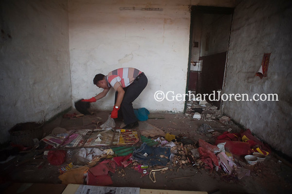 An outreach worker, sponsored by HAARP, collects used needles & syringes at a shooting gallery, Wuzhou City, Guangxi Zhuang Autonomous Region, China.