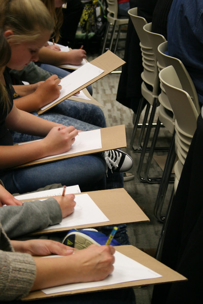 Students draw on paper.