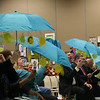 The school board looks at diagrams about the sun on umbrellas.