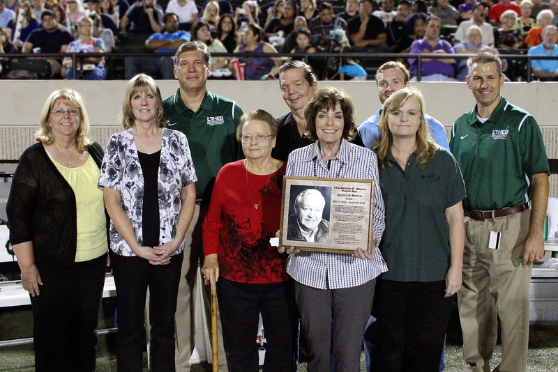 District officials and family members of the first stadium director with the plaque commemorating the dedication.