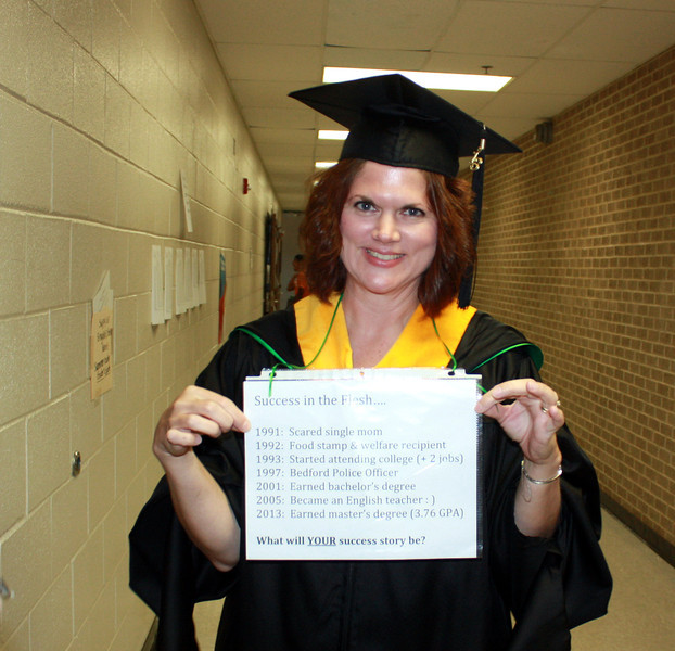 Teacher wearing graduation gown from their college.