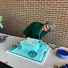 Debbe Roesler posing with cake at retirement reception.