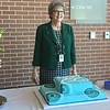 Debbe Roesler in front of cake at retirement reception.