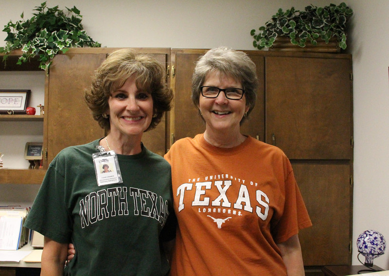 Debbe Roesler (UT shirt) with Diane Cramer (UNT shirt) on college shirt day.