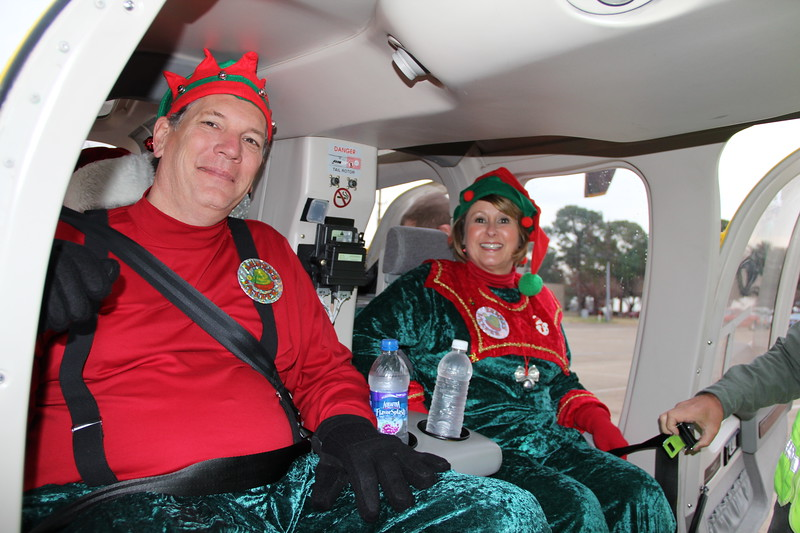 Superintendent Chapman with Mary Stokic, dressed as elves, seated in helicopter, for Santa visit to elementary schools.
