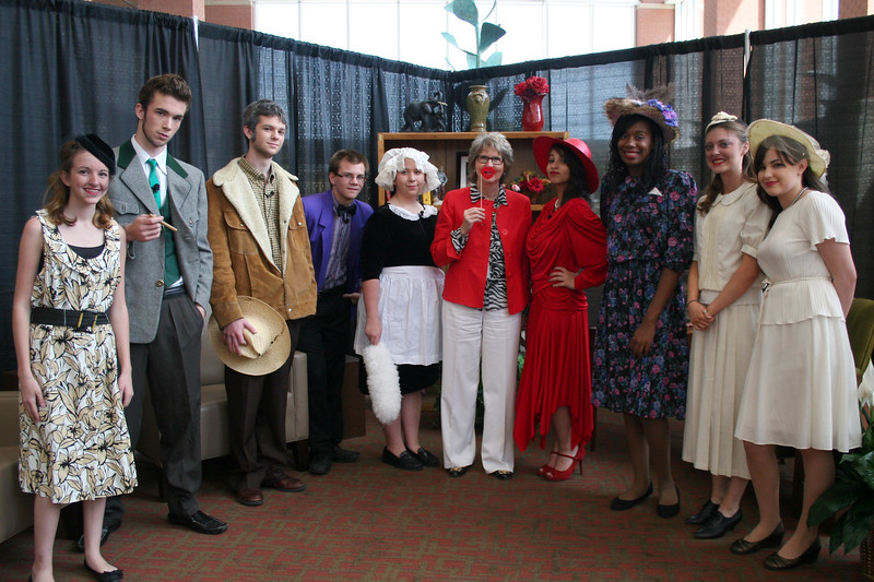 """Debbe Roesler posing with students dressed in costumes at """"Clue""""-themed luncheon."""