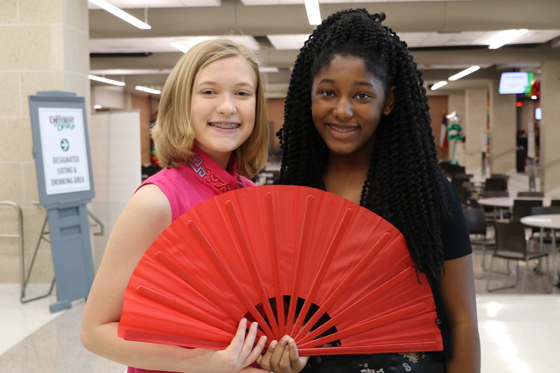 Two students with a Chinese fan.