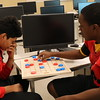 Two boys play a game of checkers.
