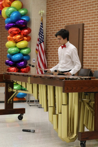 A band student plays a percussion instrument.