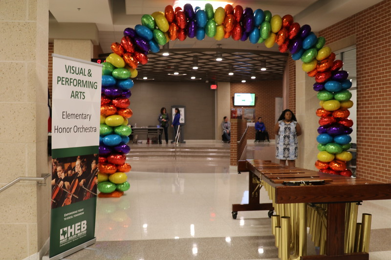 A balloon arch leading down a hallway.