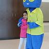 A girl hugs a mascot.