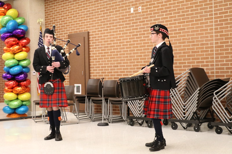 Two students play a bagpipe and a drum.