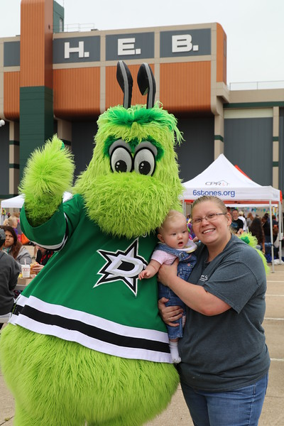A mother and baby with the Dallas Stars mascot.