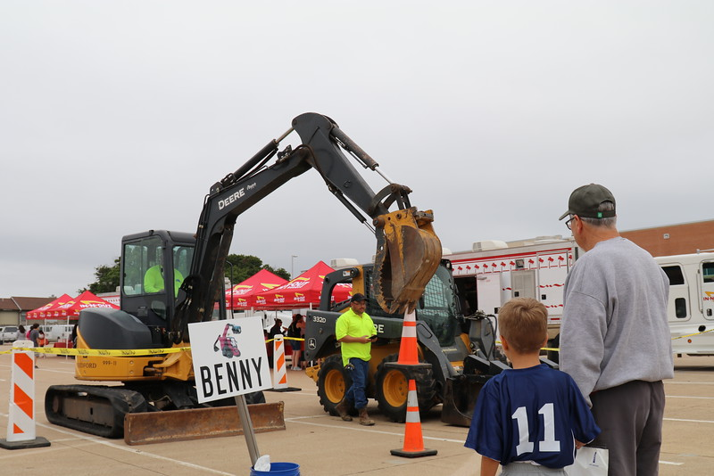 Families look at construction vehicles.