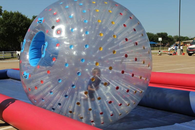 A boy runs in an inflatable hamster ball.