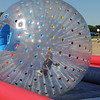 A boy runs in an inflatable hamster ball.