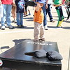 A small child plays a beanbag toss game.