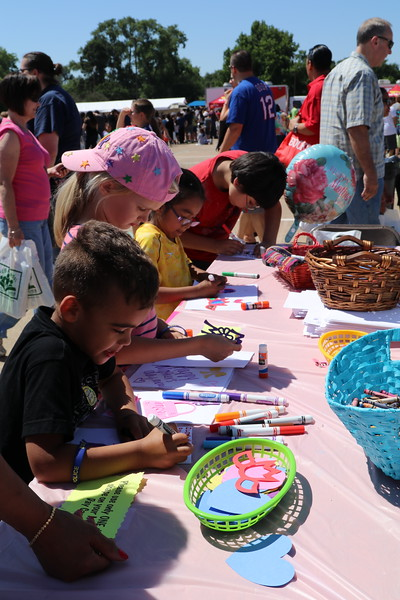 Families make crafts together using markers and paper.