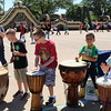 Students play drums of varying sizes.