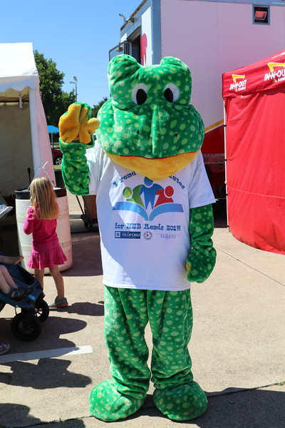 The mascot for the event waves.