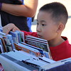 A young boy looks for a book.