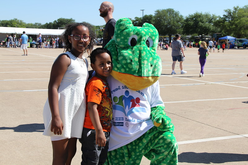Children pose with a mascot.