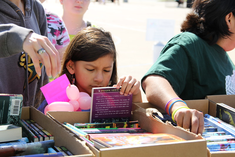 A young girl looks at the cover of a book.