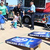 Young students play a beanbag toss with policemen.