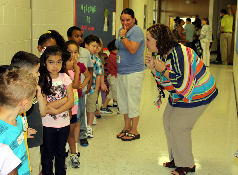 New principal talks to students in hall.